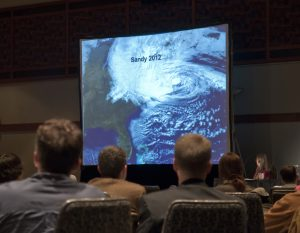 A photograph showing an audience looking at a large screen with a satellite photo of Superstorm Sandy obscuring much of the East Coast of North America