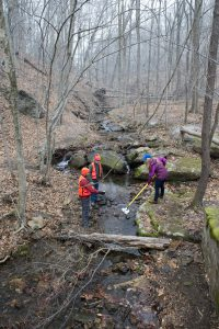 Image of three people collecting water samples from a stream in a wintery forested landscape.
