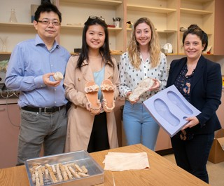 Photo of a four-person research team holding materials used to make biodegradable sandals
