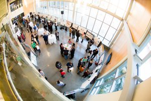 An overhead, fish-eye view of the poster session at a DENIN Graduate Research Symposium