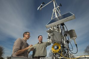 Two scientists inspect a solar-powered weather and climate observation instrument array