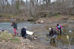 Students take measurements and sketch details of a low dam across a creak