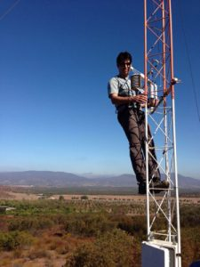 Photo of a scientist working with equipment high above ground on an instrument tower